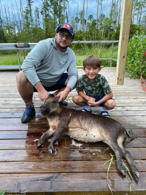 Coy and his son with a nice meat hog!! The rain had them moving yesterday!